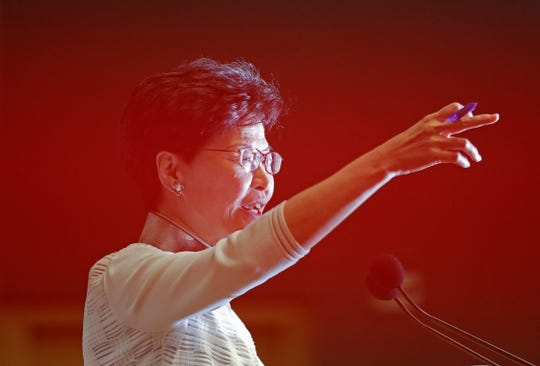 Hong Kong Chief Executive Carrie Lam gestures behind a red barrier tape during a press conference in Hong Kong Saturday.