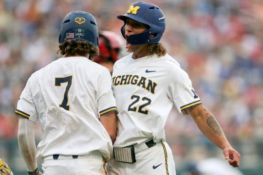 Michigan's Jesse Franklin (7) and Jordan Brewer celebrate after scoring on Jimmy Kerr's two-run triple.