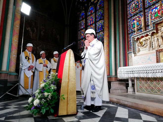 The Archbishop of Paris Michel Aupetit wears a hard-hat as he leads the first mass in a side chapel, two months after a devastating fire engulfed the Notre-Dame de Paris cathedral, Saturday June 15, 2019, in Paris.