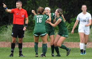 Novi forward Avery Fenchel, center, is hugged by teammates after scoring against Plymouth in the first half.
