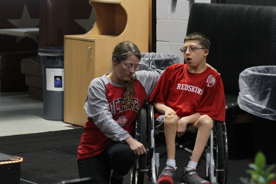 Brett Holmes along with his mom Brandy, are frequent vistors to Journey Family Amusement Center in Fremont, where Jim Tressel and Archie Griffin spoke on Friday night.