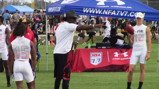 Deion Sanders instructs the Fort Myers TRUTH 7-on-7 team while Carter Land looks on before a game at Saturday's 7V7 National Championship at IMG Academy. The local team went 1-3 in pool play entering Sunday's single-elimination bracket.