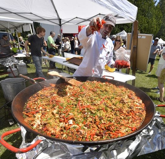 Scott McEvoy of McEvoy's Culinaria of Sister Bay adds peppers to paella prepared in an oversized wok during last year's Uncork Summer in Ellison Bay.