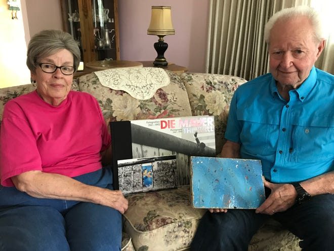 Wayne Daniels and his wife, Gayle, pose in their Great Falls home with mementos of a trip to Berlin last year. Wayne, a former Army MP who had a role in the famous standoff at Checkpoint Charlie, holds a piece of the Berlin Wall that was presented him by the U.S. Government. Gayle holds a photo the graffiti-filled wall prior to its destruction. Between the couple is a coffee table book about the Berlin Wall that was also presented to Wayne by Richard Grenell, the U.S. Ambassador to Germany.