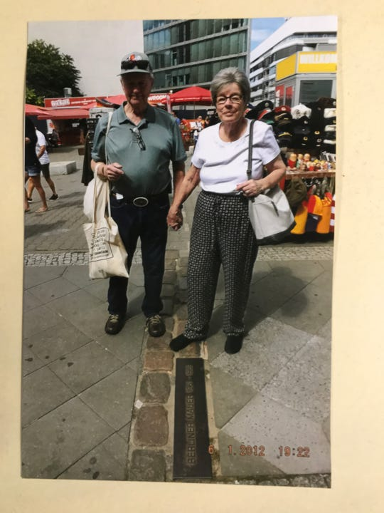 Wayne Daniels stands in what was West Germany, while his wife Gayle stands in what was East Germany during a visit to the formerly divided Berlin a few years ago. The photograph is near what was called Checkpoint Charlie during the Cold War.