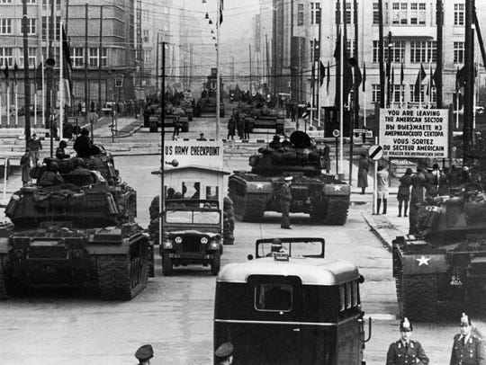 U.S. tanks approach Checkpoint Charlie during a standoff with Russian tanks in Berlin on October 27, 1961. In escort vehicle at bottom, wearing a helmet with a white stripe, is Great Falls resident Wayne Daniels.