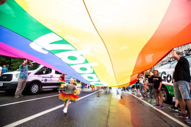 Lexi Fitzgerald, 3, runs under a giant rainbow GoDaddy flag during the 49th annual Iowa City Pride Parade, Saturday, June 15, 2019, in downtown Iowa City, Iowa.
