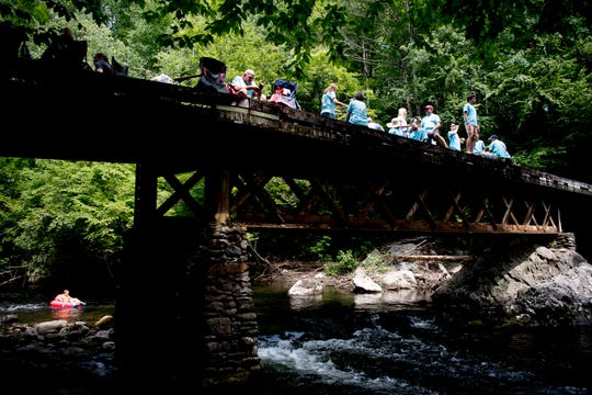 Family members relax on a bridge at Elkmont Campground in Great Smoky Mountains National Park on Saturday, June 15, 2019. The Adkerson family is celebrating 60 years of camping at the campground, reserving over 10 campsites to accommodate all of the attending family members.