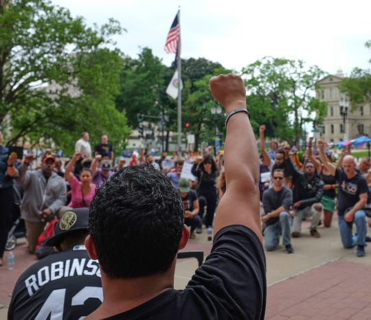 Jordan X. Evans from Black Lives Matter Lansing and other protesters take a knee in front of Lansing City Hall during the playing of the National Anthem Saturday, June 15, 2019. The crowd is protesting police butality.
