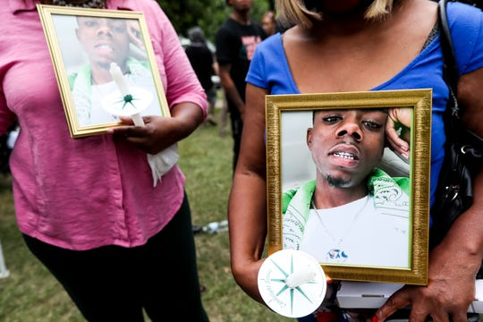 Community members hold photos of Brandon Webber on Friday, June 14, 2019.  While attempting to serve a warrant, U.S. Marshals Service task force shot and killed Webber on Wednesday, June 12, 2019, sparking a riot that injured members of the Memphis Police Department and Shelby County Sheriff's Office.