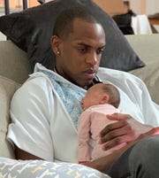 Khris Middleton holds his daughter, Audrielle, who was born the day after the Bucks clinched their first playoff series win since 2001.