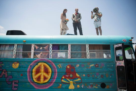 Brittany Wood and Kevin Atkins, both of Lewisburg, Tenn., get married by captain of the Roo Bus Daniel Horton of Huntsville, Ala. on top of the Roo Bus at Bonnaroo Music and Arts Festival in Manchester, Tenn., Saturday, June 15, 2019.