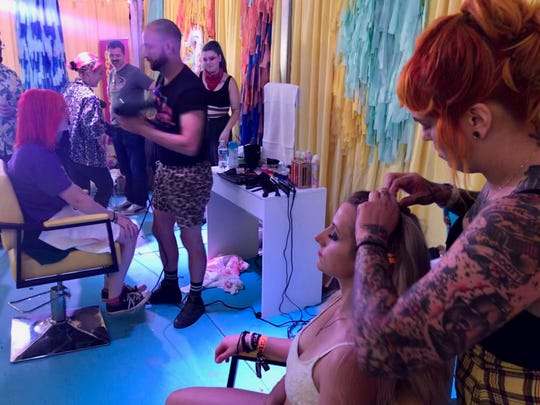Alise Merry of Louisville, Ky., gets her hair styled by Grace Moser at Bonnaroo Music and Arts Festival in the campground experience curated by Hayley Williams of Paramore. In the background, stylist Brian O'Connor of Good Dye Young does the hair of excited Paramore fan Emily Meyer.