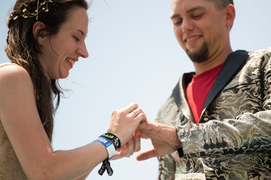 Brittany Wood places a ring on Kevin Atkins' finger, both of Lewisburg, Tenn., while getting married on top of the Roo Bus at Bonnaroo Music and Arts Festival in Manchester, Tenn., Saturday, June 15, 2019.