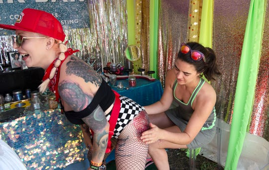 Callie Gray puts glitter on Shush Stonebreaker's body at Bioglitz tent at Sanctuary Of Self Love (Plaza 2) campground at Bonnaroo Music and Arts Festival on Saturday, June 15, 2019 in Manchester, Tenn.  Sanctuary Of Self Love was curated by Hayley Williams of Paramore.