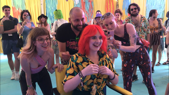 Hayley Williams (left), frontwoman of the rock band Paramore, takes part in a makeover reveal at Bonnaroo Music and Arts Festival. Next to her is stylist Brian O'Connor of Good Dye Young, and excited fan Emily Meyer.