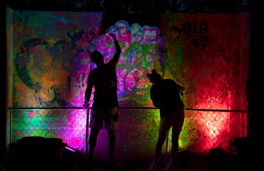 Eddy Sidani and Victoria Krugel paint a on a glow in the dark mural in Where in the Woods, a new campground experience,  at during Bonnaroo Music and Arts Festival on Friday, June 14, 2019 in Manchester, Tenn.