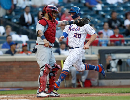 St. Louis Cardinals catcher Yadier Molina gestures toward the runner at third base as New York Mets' Pete Alonso (20) scores on Todd Frazier's single during the first inning of a game Friday, June 14, 2019, in New York.