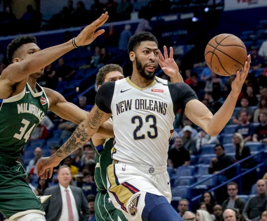 FILE - In this Tuesday, March 12, 2019 file photo, New Orleans Pelicans forward Anthony Davis (23) takes an outlet pass against Milwaukee Bucks forward Giannis Antetokounmpo (34) in the first half of an NBA basketball game in New Orleans.
