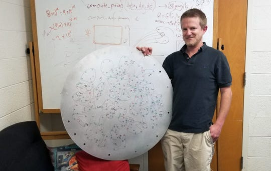 "MSU astronomy graduate student Drew Chojnowski holds a plate utilized to pinpoint different stars. The plate, an essential ""map of the sky,"" is loaded into the telescope at Apache Point Observatory, and was a key element in studying the highly magnetic stars at the center of Chojnowski's discovery."