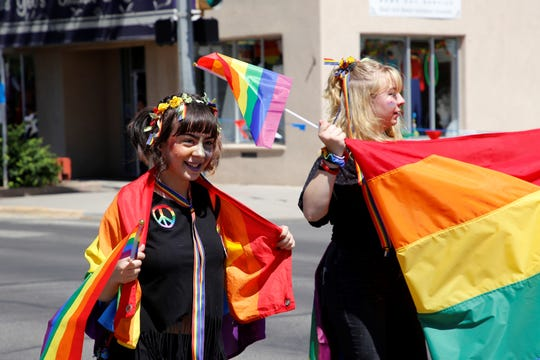 Megan Henderson, left, and Bri Heath of Farmington celebrate Pride Month walking down Main Street during Saturday's fourth annual parade in downtown Farmington.