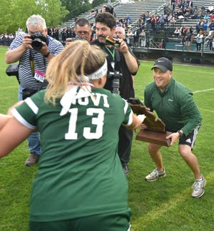 As he holds the Div. 1 Michigan Girls Soccer state title trophy in his arms - Novi coach Todd Pheiffer is about to get mobbed by his team.