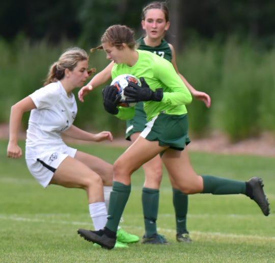 Novi goalie Sammy Maday runs forward to scoop up the ball as it gets near her net.