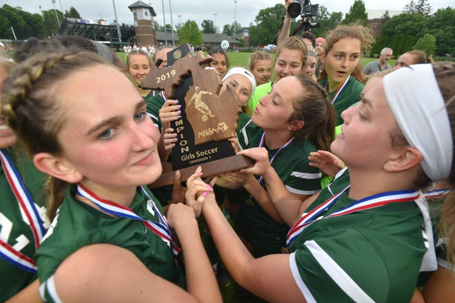 The Novi Wildcats hold and prepare to plant a few kisses on their soccer state title trophy.