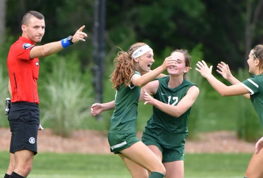 As the referee signals that play will commence at midfield, Avery Fenchel celebrates her second goal with her teammates.