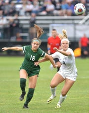 Novi Wildcat Jessie Bandyk, left, and Plymout Wildcat Audrey Kananen tear after the ball during their Div. 1 state girls soccer final on June 15 at MSU. Novi won the match and their second straight title, 5-0.