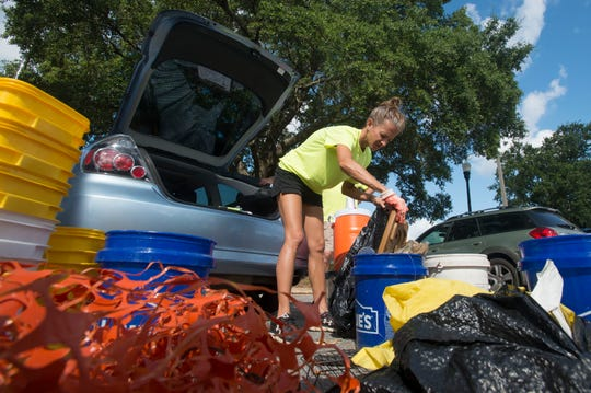 Jen Deubler of Ocean Hour Florida, sorts through and counts trash during a previous cleanup of Wayside Park and the Graffiti Bridge area.