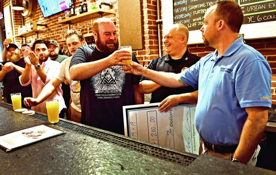 Kevin Eck, right, of York County Veterans Outreach, serves Jared Barnes, a Navy veteran, of Collusion Tap Works, a glass of York City 6 Volume 2, a mango session IPA, during a press conference at Collusion Tap Works in York City, Saturday, June 15, 2019. The six York City breweries--Mudhook Brewery, Liquid Hero Brewery, Crystal Ball Brewing Company, Collusion Tap Works, Gift Horse Brewing Company and Old Forge Brewing Company--will donate one dollar from each pint sold at each of the breweries to York County Veterans Outreach. Dawn J. Sagert photo