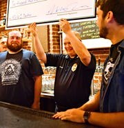York City Police Chief Troy Bankert accepts a check for $1200 from York City 6 brewing collaborative from their first collaborative brewing project during a press conference unveiling Volume 2, a mango session IPA, at Collusion Tap Works in York City, Saturday, June 15, 2019. The six York City breweries--Mudhook Brewery, Liquid Hero Brewery, Crystal Ball Brewing Company, Collusion Tap Works, Gift Horse Brewing Company and Old Forge Brewing Company--will donate one dollar from each pint sold at each of the breweries to York County Veterans Outreach. Dawn J. Sagert photo