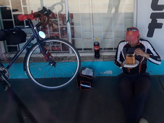 Cornel Mancas of York stops to eat a meal along a street in a town in Namibia during his bicycle trip across Africa in 2018. Mancas cycled from the southern tip to the northern tip of Africa, pedaling more than 7,00 miles.