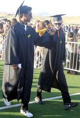 Marcus Young (left) and Ryan Bates bump fists as they walk toward the ceremony.