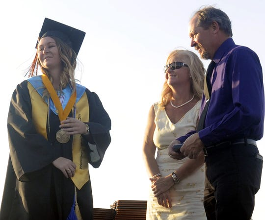 Salutatorian Sabrina McCallum accepts a medal of recognition as her parents look on.