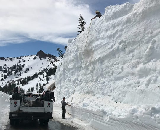 Two members of park road crew measure a 28 foot high snow drift near Emerald Lake along the park highway at Lassen Volcanic National Park.
