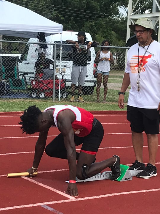 River Cities standout Liquesni October prepares to start the boys 4x100 relay as Juan Plaza looks on.