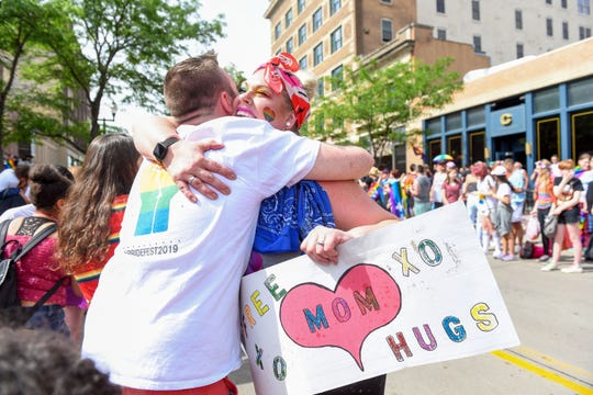 """A spectator runs forward to hug a woman with a """"free mom hugs"""" sign at the first-ever Pride parade Saturday, June 15, in downtown Sioux Falls."""