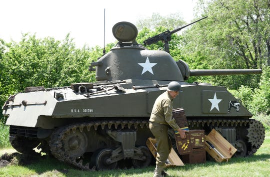 A WWII reenactor begins to prep an M14 Sherman tank for a military vehicle parade Saturday, June 15 at Stearns History Museum.