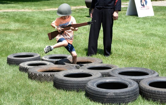 AJ Morris runs through an obstacle course during a WWII reenactment Saturday, June 15 at Stearns History Museum.