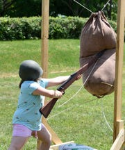 Emma Cruz practices her weaponry on the obstacle course during a WWII reenactment Saturday, June 15 at Stearns History Museum.