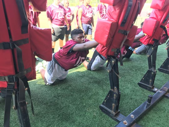 Defensive lineman Dequaveon Fuller hits the blocking sled during the Willie Taggart All-Position Camp on Saturday, June 15, 2019.