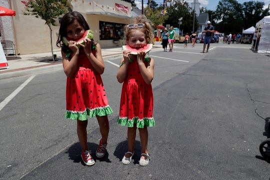 Olivia Futrell, 5, left, and her sister Harper Futrell, 4, bite into their fresh watermelon slices during Montiello's 69th Annual Watermelon Festival Saturday.