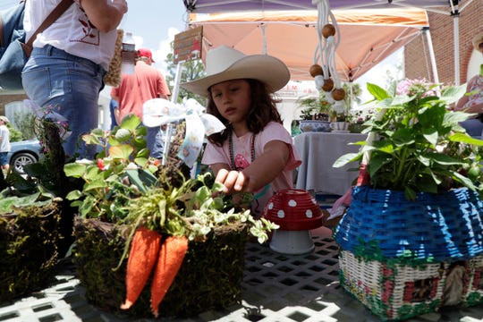 Mikayla Hopkins, 7, checks out a fairy garden during Monticello's 69th Annual Watermelon Festival Saturday, June 15, 2019.