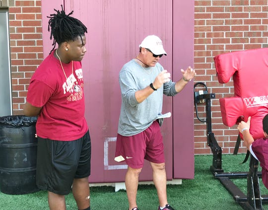 Florida State defensive lineman Quashon Fuller (left) and assistant coach Mark Snyder observe as players hit the blocking sled.