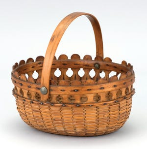 This double lollipop basket was made in the early 20th century. It is 4 1/2 inches high, 9 inches long and 8 1/4 inches wide with a swing handle. It was estimated at $40,000 to $60,000 but did not sell.