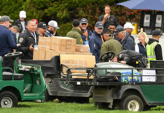 A golf cart loaded with boxes, which was involved in an incident, is inspected on the 16th fairway.