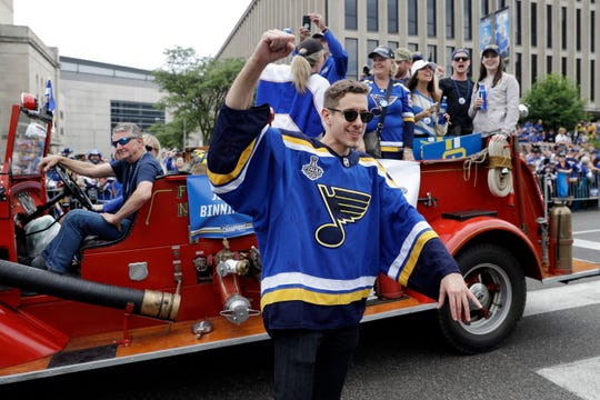 Goalie Jordan Binnington gets off of a fire truck to greet fans.