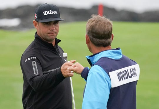 Gary Woodland, left, is congratulated by caddie Brennan Little after making a birdie on the ninth green.